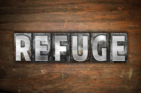 refuge: The word Refuge written in vintage metal letterpress type on an aged wooden background.