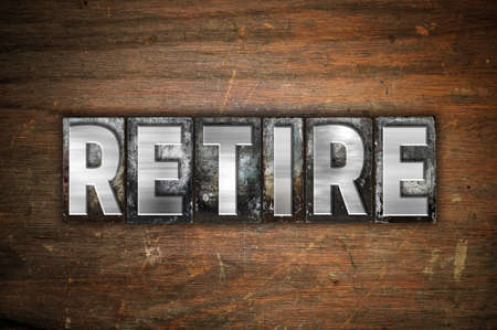 retiring: The word Retire written in vintage metal letterpress type on an aged wooden background. Stock Photo