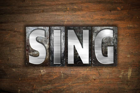 The word Sing written in vintage metal letterpress type on an aged wooden background.