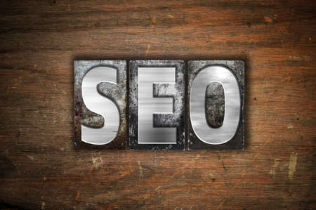 The word SEO written in vintage metal letterpress type on an aged wooden background.