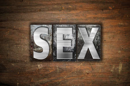 The word Sex written in vintage metal letterpress type on an aged wooden background.