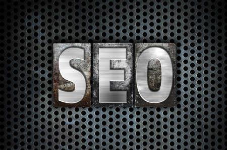 The word SEO written in vintage metal letterpress type on a black industrial grid background.