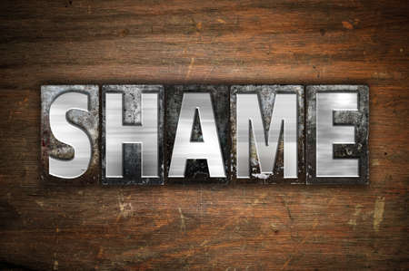 humiliation: The word Shame written in vintage metal letterpress type on an aged wooden background.