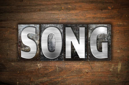 chorale: The word Song written in vintage metal letterpress type on an aged wooden background.