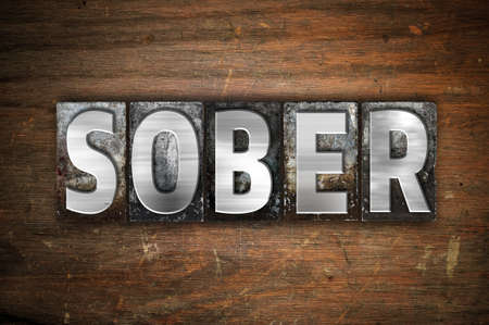 The word Sober written in vintage metal letterpress type on an aged wooden background. Stock Photo