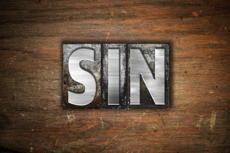 The word Sin written in vintage metal letterpress type on an aged wooden background.