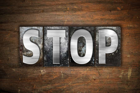 stoppage: The word Stop written in vintage metal letterpress type on an aged wooden background.