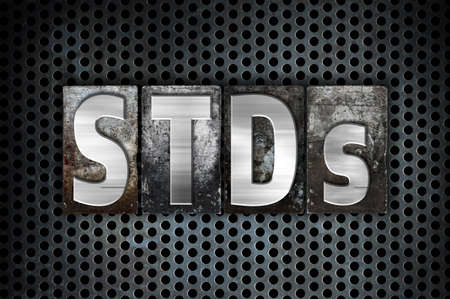 The word STDs written in vintage metal letterpress type on a black industrial grid background. Stock Photo