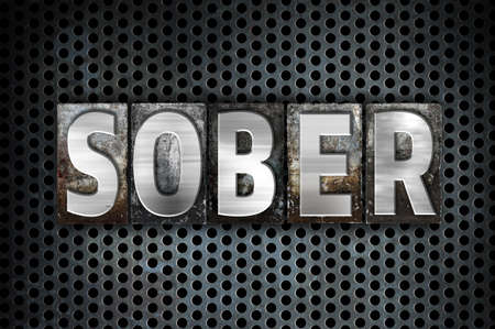 The word Sober written in vintage metal letterpress type on a black industrial grid background. Stock Photo