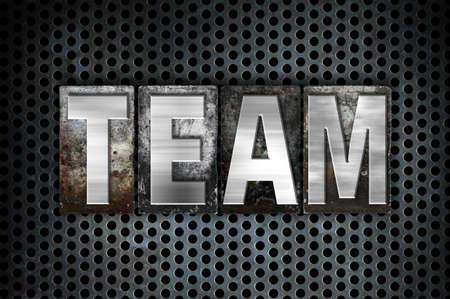 teammate: The word Team written in vintage metal letterpress type on a black industrial grid background. Stock Photo
