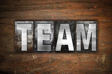 """Das Wort """"Team"""" im Vintage-Metall-Buch-Typ auf einem gealterten hölzernen Hintergrund geschrieben."""