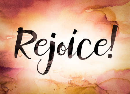 The word Rejoice written in black paint on a colorful watercolor washed background. Banco de Imagens