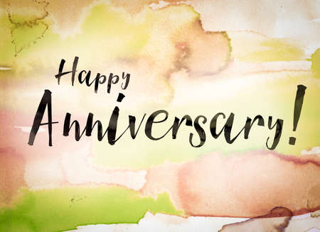The word Happy Anniversary written in black paint on a colorful watercolor washed background. Stock Photo