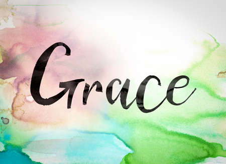 The word Grace written in black paint on a colorful watercolor washed background. Imagens