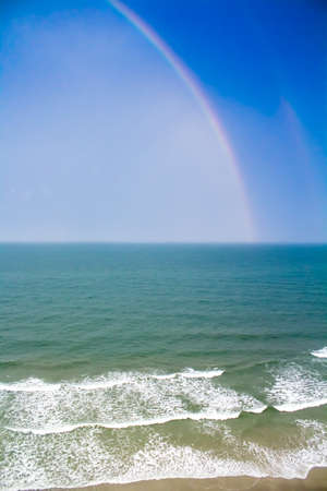 crashing: A colorful rainbow after a thunderstorm over crashing beach waves.