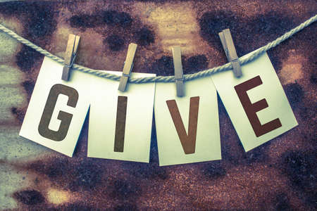 lend a hand: The word GIVE stamped on card stock hanging from old twine and clothes pins over a rusty vintage background. Stock Photo