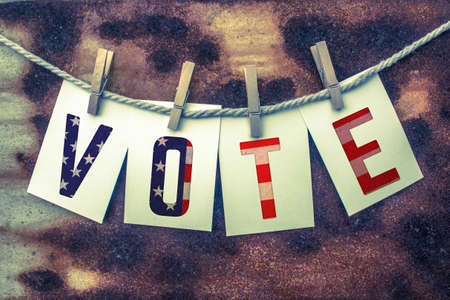 clothes pins: The word VOTE stamped on card stock hanging from old twine and clothes pins over a rusty vintage background.