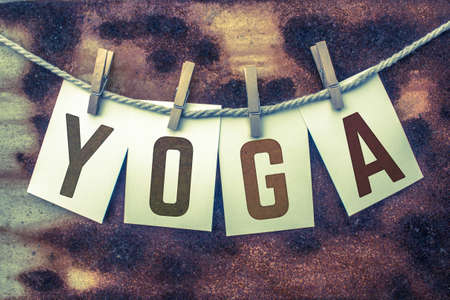 clothes pins: The word YOGA stamped on card stock hanging from old twine and clothes pins over a rusty vintage background. Stock Photo