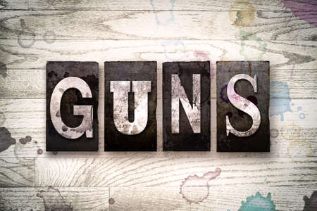 muzzleloader: The word GUNS written in vintage dirty metal letterpress type on a whitewashed wooden background with ink and paint stains. Stock Photo