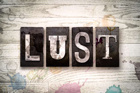 seven deadly sins: The word LUST written in vintage dirty metal letterpress type on a whitewashed wooden background with ink and paint stains.