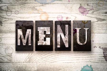 """Het woord """"MENU"""" geschreven in vintage vuile metalen boekdruk type op een witgekalkte houten achtergrond met inkt en verf vlekken. Stockfoto"""