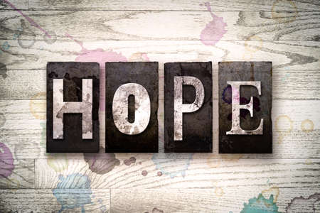 anticipate: The word HOPE written in vintage dirty metal letterpress type on a whitewashed wooden background with ink and paint stains. Stock Photo