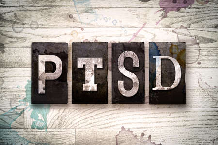 whitewashed: The word PTSD written in vintage dirty metal letterpress type on a whitewashed wooden background with ink and paint stains. Stock Photo