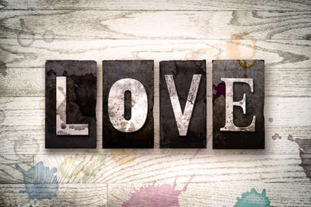 The word LOVE written in vintage dirty metal letterpress type on a whitewashed wooden background with ink and paint stains.