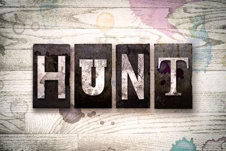 """Das Wort """"HUNT"""" geschrieben in Vintage schmutzig Metall-Buch-Typ auf einem weißen hölzernen Hintergrund mit Tinte und Farbflecken."""
