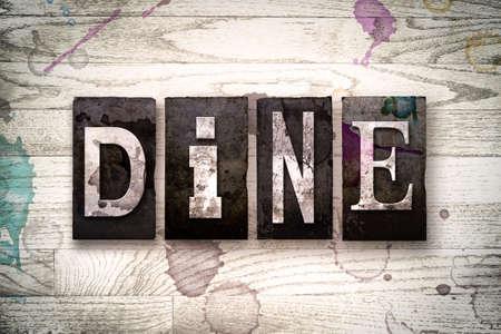 """Het woord """"DINE"""" geschreven in vintage vuile metalen boekdruk letters op een witte houten achtergrond met inkt en verf vlekken."""