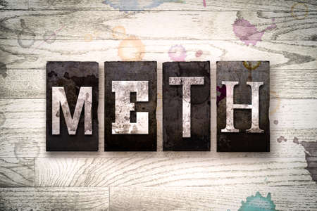meth: The word METH written in vintage dirty metal letterpress type on a whitewashed wooden background with ink and paint stains. Stock Photo