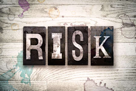 The word RISK written in vintage dirty metal letterpress type on a whitewashed wooden background with ink and paint stains.