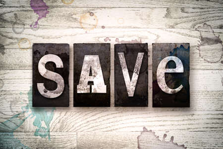 The word SAVE written in vintage dirty metal letterpress type on a whitewashed wooden background with ink and paint stains. Stock Photo
