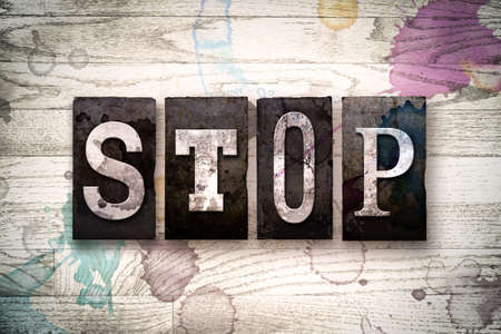 conclude: The word STOP written in vintage dirty metal letterpress type on a whitewashed wooden background with ink and paint stains. Stock Photo