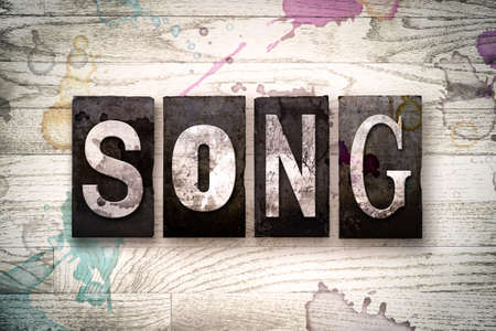 chorale: The word SONG written in vintage dirty metal letterpress type on a whitewashed wooden background with ink and paint stains.