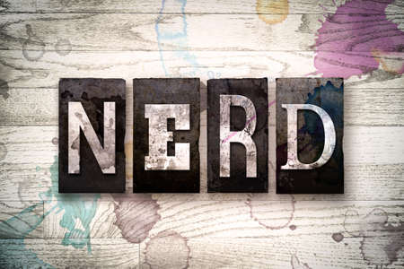 dweeb: The word NERD written in vintage dirty metal letterpress type on a whitewashed wooden background with ink and paint stains. Stock Photo