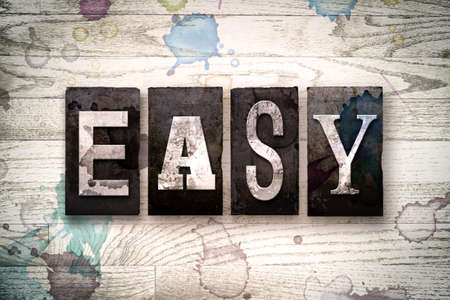 The word EASY written in vintage dirty metal letterpress type on a whitewashed wooden background with ink and paint stains. Stock Photo