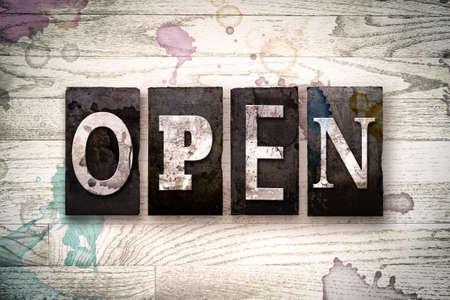 """Het woord """"OPEN"""" geschreven in vintage vuile metalen boekdruk type op een witgekalkte houten achtergrond met inkt en verf vlekken. Stockfoto"""