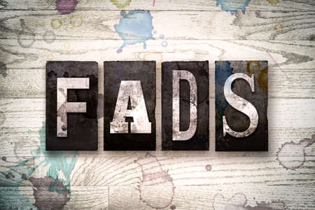craze: The word FADS written in vintage dirty metal letterpress type on a whitewashed wooden background with ink and paint stains.