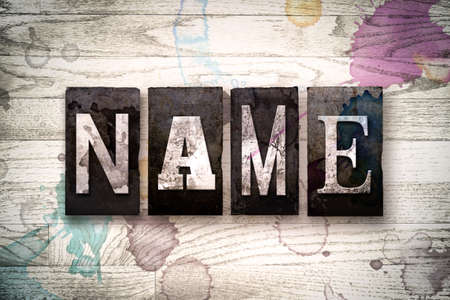 surname: The word NAME written in vintage dirty metal letterpress type on a whitewashed wooden background with ink and paint stains.