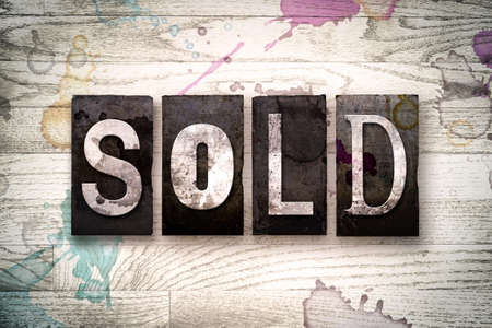selling service: The word SOLD written in vintage dirty metal letterpress type on a whitewashed wooden background with ink and paint stains. Stock Photo