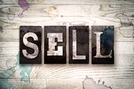 selling service: The word SELL written in vintage dirty metal letterpress type on a whitewashed wooden background with ink and paint stains.