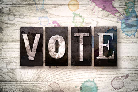 The word VOTE written in vintage dirty metal letterpress type on a whitewashed wooden background with ink and paint stains. Stok Fotoğraf