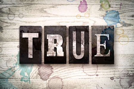 factual: The word TRUE written in vintage dirty metal letterpress type on a whitewashed wooden background with ink and paint stains. Stock Photo