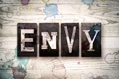 """La palabra """"ENVIDIA"""" escrita en el tipo de tipografía de metal sucio de la vendimia en un fondo de madera blanqueada con manchas de tinta y pintura."""