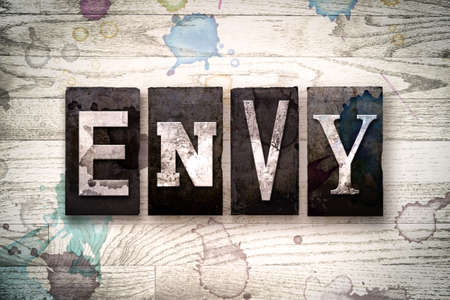 The word ENVY written in vintage dirty metal letterpress type on a whitewashed wooden background with ink and paint stains.