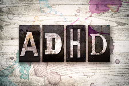 hyperactivity: The word ADHD written in vintage dirty metal letterpress type on a whitewashed wooden background with ink and paint stains. Stock Photo