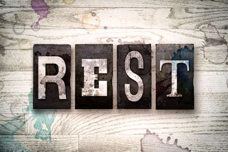 restful: The word REST written in vintage dirty metal letterpress type on a whitewashed wooden background with ink and paint stains.