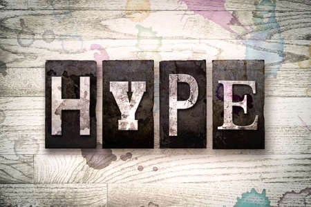 hype: The word HYPE written in vintage dirty metal letterpress type on a whitewashed wooden background with ink and paint stains. Stock Photo