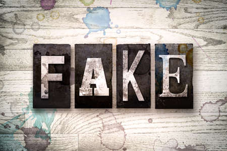 scamming: The word FAKE written in vintage dirty metal letterpress type on a whitewashed wooden background with ink and paint stains. Stock Photo